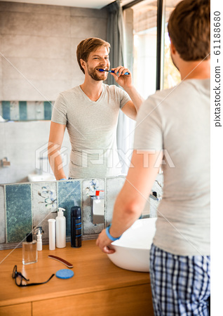 Handsome young man brushing teeth in the morning 61188680
