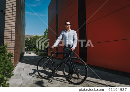 Happy executive cycling in city stock photo 61194927
