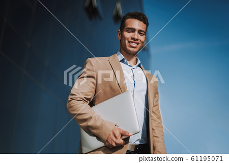 Happy young man with laptop in street stock photo 61195071