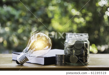 Energy saving light bulb with coins in glass jar 61195519