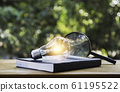 Light bulb and a book on table and copy space for 61195522