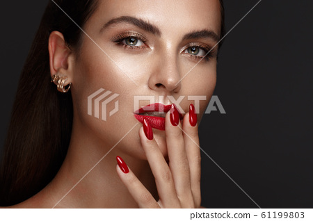Beautiful girl with a classic make-up and red nails. Manicure design. Beauty face. 61199803