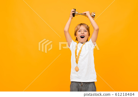 happy boy in a t-shirt with a medal on his neck raises the winner's cup on a yellow background with 61218484