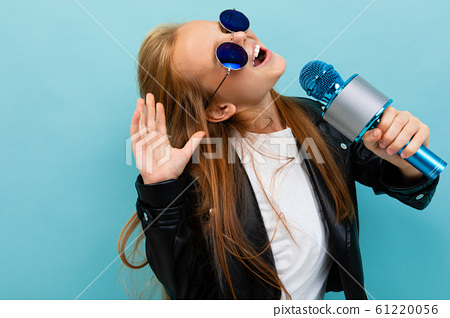 Nice girl in black jacket, blue sunglasses sings songs with blue microphone isolated on blue 61220056