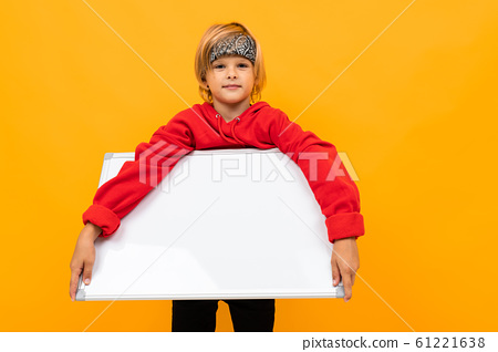 stylish boy child with a bandana on his head holds a poster with a layout on a yellow background 61221638