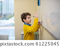 Boy writing on the whiteboard with marker 61225045