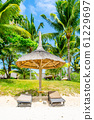 Beach sunbeds with straw parasol under the palm trees. Romantic summer holiday and relax. Tranquil and calm scene in tropical paradise 61229697
