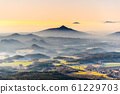 Ralsko Mountain rising from the mist. Weather temperature inversion in Central Bohemian Uplands, Czech Republic 61229703