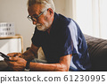 Senior man sitting alone for relaxation and smile portrait in home. 61230995