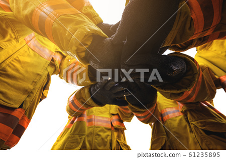 Firefighter putting hands up for fire fighting, Teamwork concept 61235895