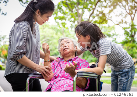 Sick senior grandmother in wheelchair with epileptic seizures in outdoor,elderly patient convulsions suffering from illness with epilepsy during seizure attack,asian daughter,granddaughter crying,fami 61246363