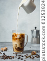 Iced latte coffee in cup glass with pouring milk 61253924