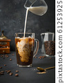 Iced latte coffee in cup glass with pouring milk on black 61253925
