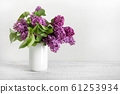 Bouquet of purple lilac flowers in white vase. Space for text. 61253934