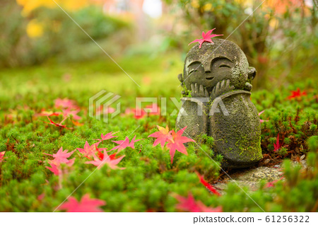 Red Maple leaf on head of Jizo sculpture doll 61256322
