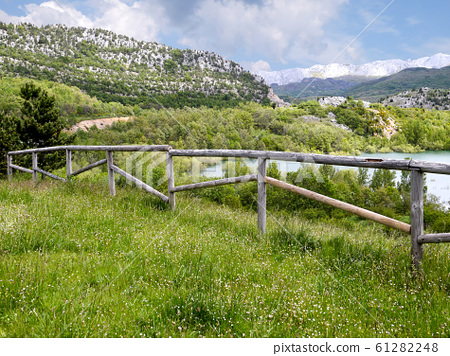 Mountain landscape with wooden fence and lake 61282248
