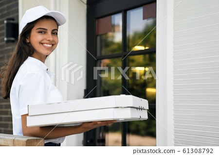 Smiling deliverywoman holding boxes of pizza. 61308792