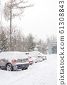 extreme snowfall with cars coverd with a lot of 61308843