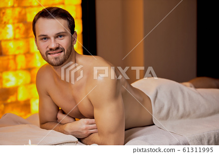 Handsome caucasian man lying on massage table at spa center 61311995