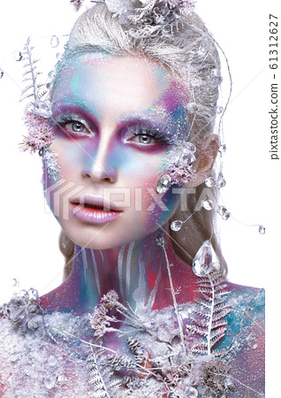 Beautiful girl in the image of a snowy unicorn creature. Creative make up. Art look. 61312627