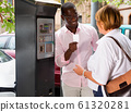 Polite intelligent African man helping middle aged woman to buy ticket in parking meter on summer city street 61320281