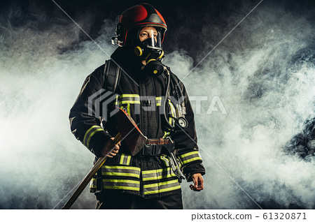 caucasian fireman with hammer risking his life to save people from fire 61320871
