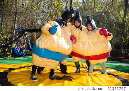 Friends posing in inflatable sumo suits 61321767