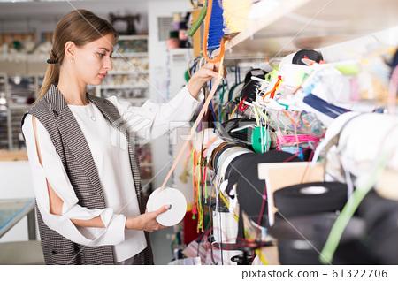 Girl choosing ribbons for needlecraft 61322706