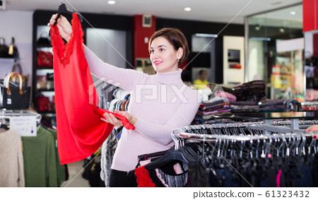 Woman choosing pretty dress 61323432