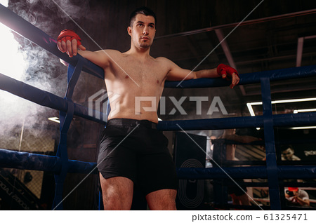 serious muscular man after active fight 61325471