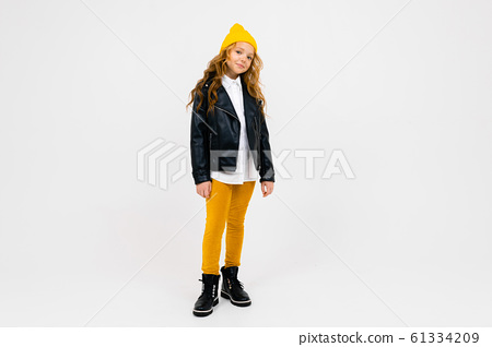 stylish caucasian charming schoolgirl in a white shirt, leather black jacket, with a yellow cap on 61334209
