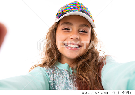portrait of a charming caucasian girl with a beautiful smile in a baseball cap on a white background 61334695