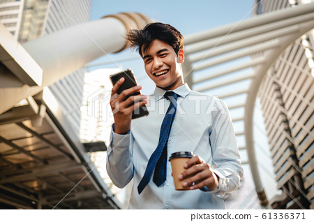 Portrait of a Happy Young Businessman Using Mobile Phone 61336371