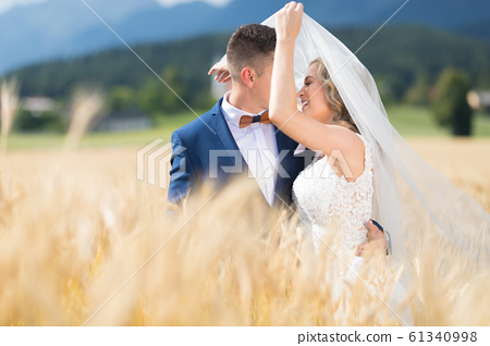 Groom hugs bride tenderly while wind blows her veil in wheat field somewhere in Slovenian countryside. 61340998