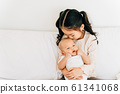 Asian child hugging newborn baby on bed 61341068