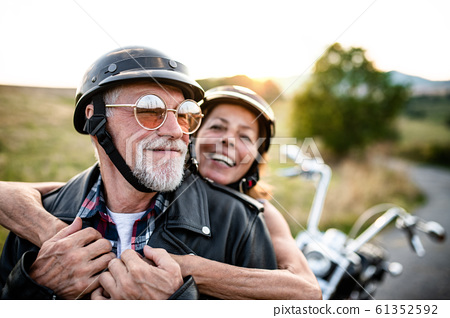 A cheerful senior couple travellers with motorbike in countryside. 61352592