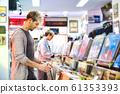 Young Man Choosing Vintage Vinyl LP In Records Shop 61353393