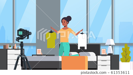 fashion blogger holding hangers with clothes african american woman recording online video live streaming social media blogging concept modern bedroom interior portrait horizontal 61353611