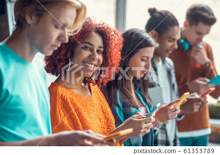 Student smiling standing near friends and using social media 61353789