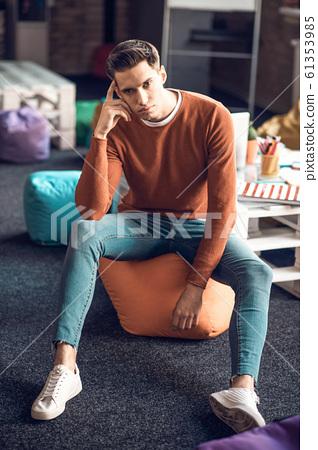 Student sitting on beanbag chair having little break from studying 61353985