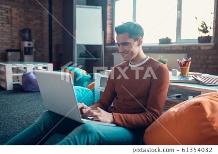 Cheerful handsome freelancer feeling good while working at home 61354032