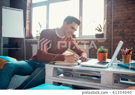 Handsome student smiling while enjoying studying process at home 61354040