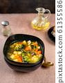 Spring vegetable soup in a black bowl 61355586