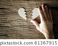 woman hand holding broken heart paper cut on wooden background 61367915
