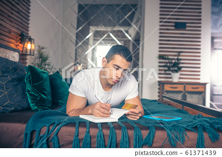 Guy lying on the bed writing a credit card number. 61371439