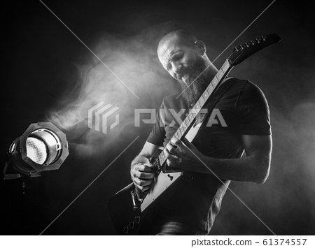 Bearded man playing guitar with spotlight 61374557