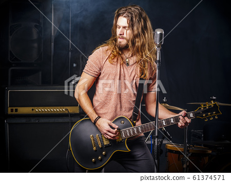 Young man playing electric guitar on stage 61374571