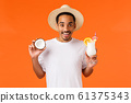 Tourism, vacation and leisure concept. Attractive chilling and relaxed african-american male in white t-shirt, summer hat, holding coconut and alcohol drink, drinking cocktail enjoying trip 61375343