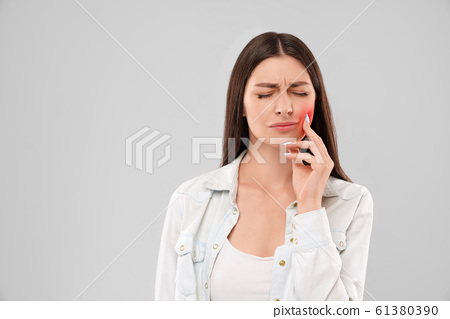 Woman touching mouth because of toothache. 61380390