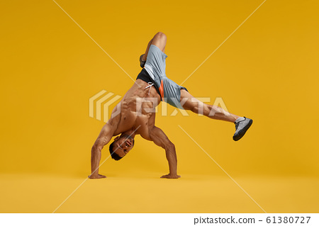 Muscular young man performing handstand stunt 61380727